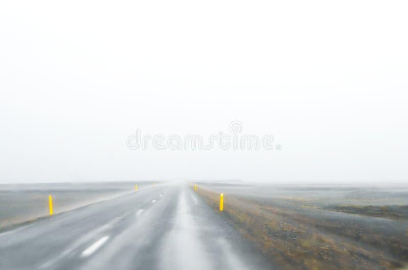 Island - September, 2014 - väg för med is dimma i Island den västra delen, molnig väg för mist royaltyfri foto