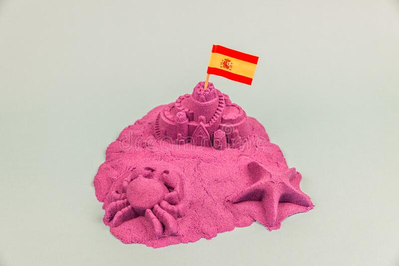 An island with Spain flag on a sand castle.  royalty free stock image