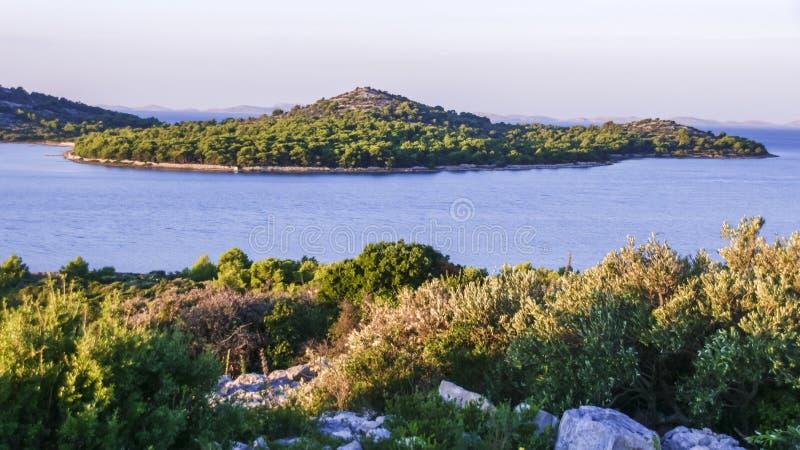 Island in sunrise rays in Adriatic sea near Zminjak, Croatia stock photo
