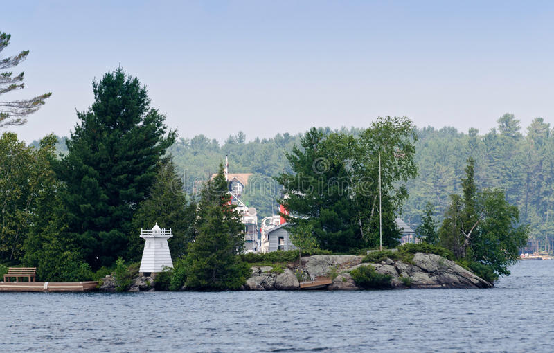 Island with a toy lighthouse. And a cottage behind royalty free stock image