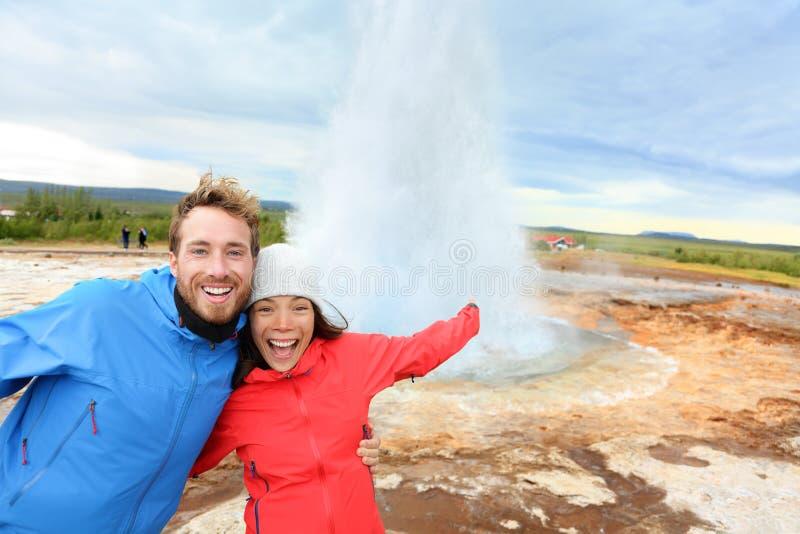 Island turister som är roliga vid den Strokkur geyseren royaltyfria foton