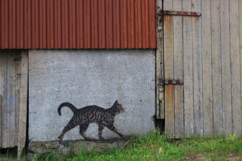 On the island Utsira, Norway. A street Artist painted a cat on the wall of a barn. Utsira is a small island in the North Sea, about 18 kilometers West of stock images