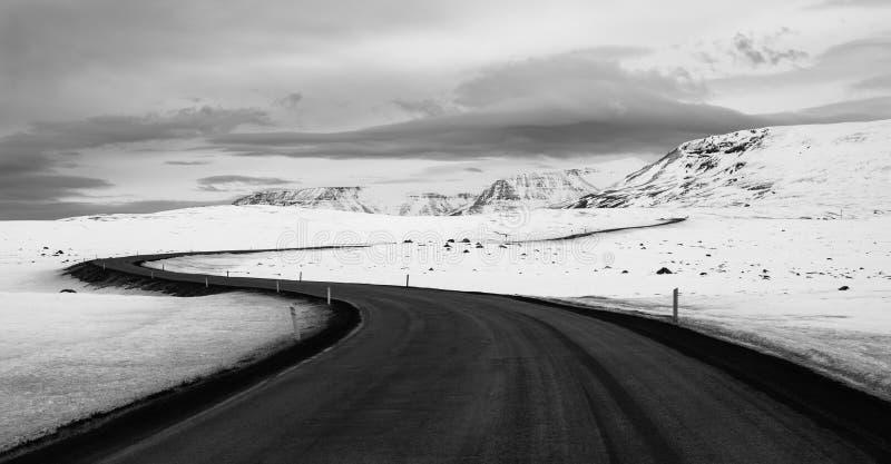 Island väg i vintertiden Med sn? t?ckte berg i bakgrunden Svartvit plats arkivfoton