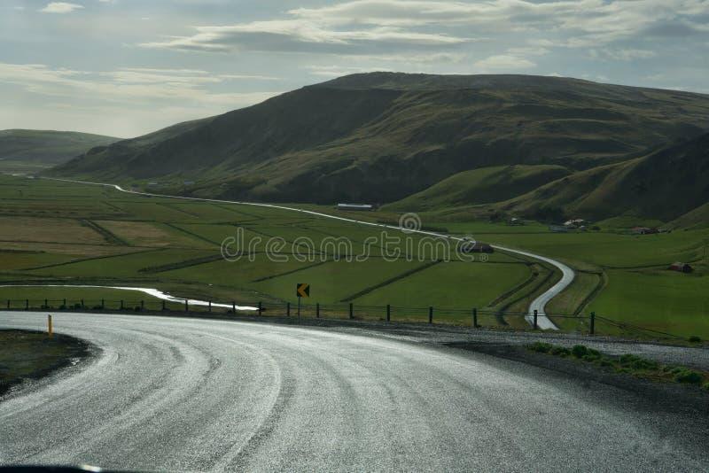 Islandia: campos agrícolas, río, montañas y caminos curvy foto de archivo libre de regalías
