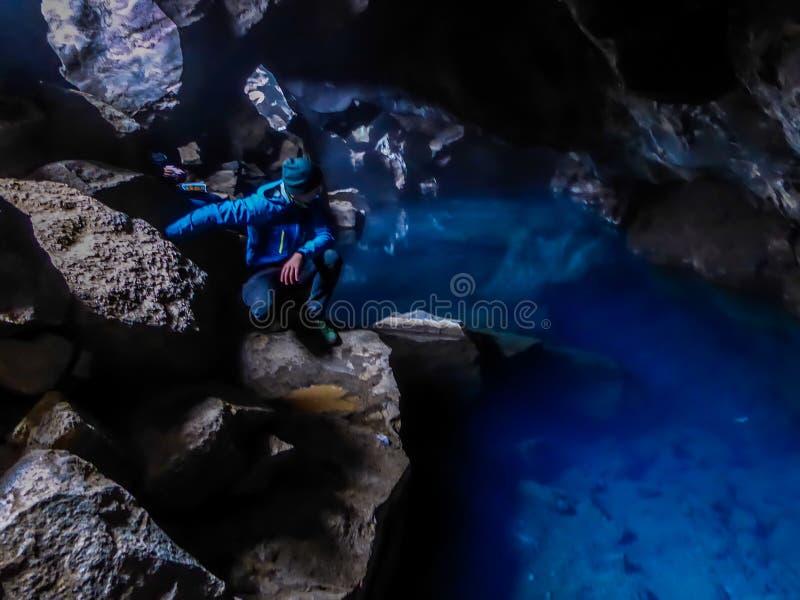 Islandia - hombre joven en la cueva del ¡del tagjà del ³ de Grjà con extremadamente agua del bue imagen de archivo libre de regalías