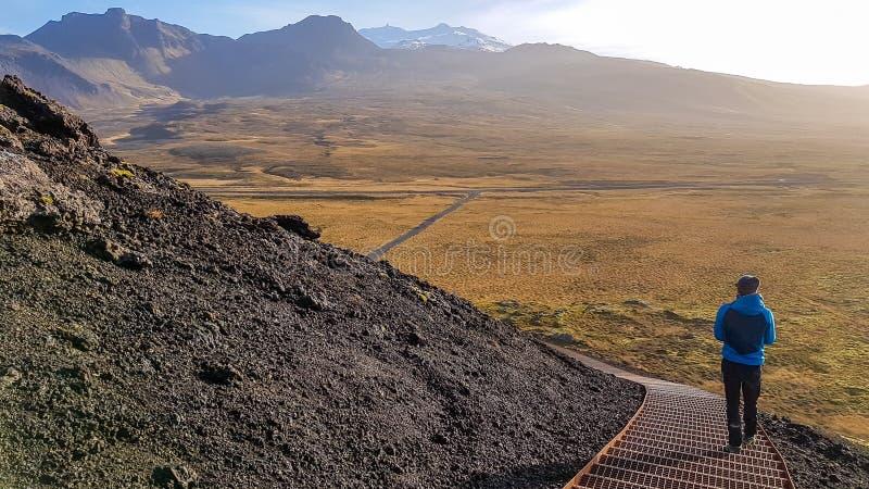 Islandia - hombre joven que camina abajo del volc?n imagen de archivo libre de regalías