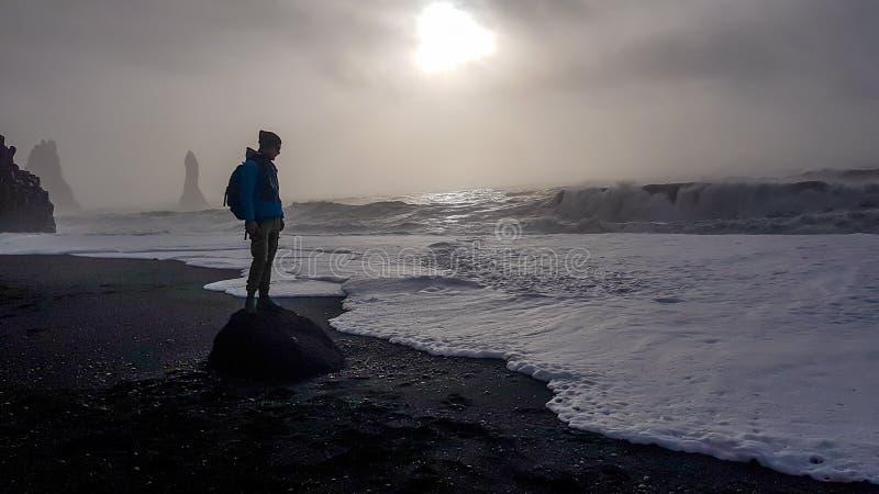 Islandia - situaci?n del hombre joven en ?l Reynisfara fotos de archivo