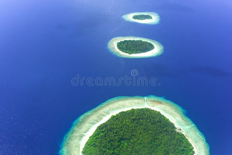 Islands in Baa Atoll, Maldives, Indian Ocean. Island chain in Baa Atoll in the Maldives, Indian Ocean with blue waters on sunny day royalty free stock image