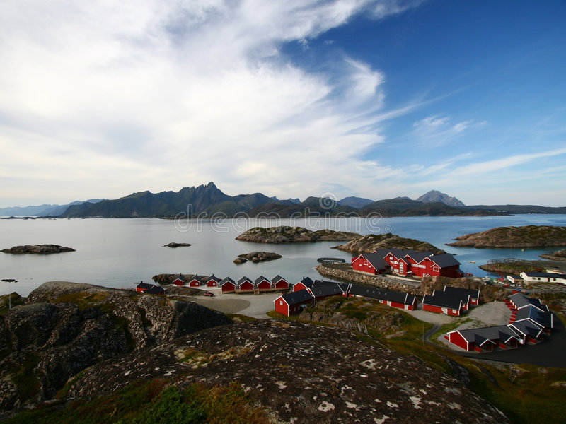 Islands and red chalets, norway. Typical red fishing chalets in the lofoten islands during summer, Norway royalty free stock photography