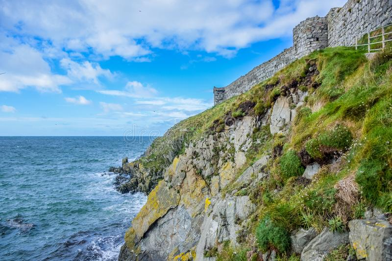 Isle of Man seashore landscape covered with green grass and great wall of Peel Castle in Peel city, Isle of Man. Isle of Man seashore landscape covered with stock image