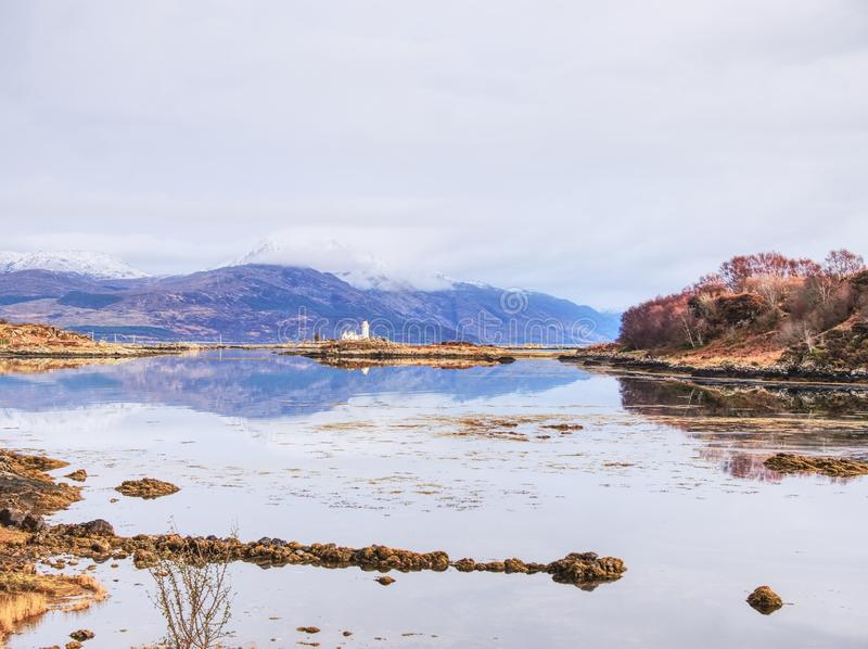 Isle Ornsay with white tower of Lighthouse; Isle of Skye; Scotland. Sunny winter day with snowy mountains stock photography