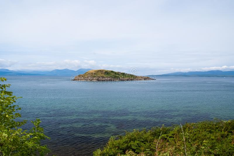 Isle in sea in Oban, United Kingdom. Archipelago on idyllic sky. Summer vacation on island. Adventure and discovery. Travelling and wanderlust royalty free stock images