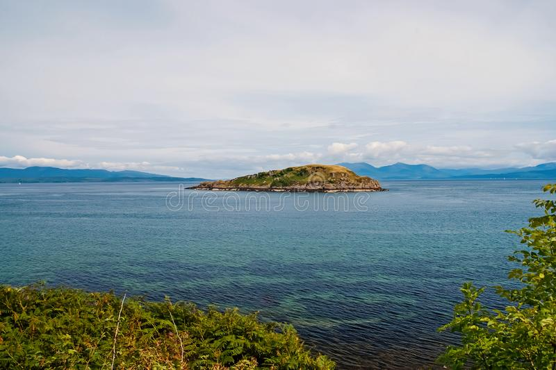 Isle in sea in Oban, United Kingdom. Archipelago on idyllic sky. Summer vacation on island. Adventure and discovery. Travelling and wanderlust royalty free stock photography