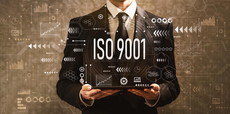 ISO 9001 com o homem de negócios que guarda um tablet pc imagens de stock royalty free