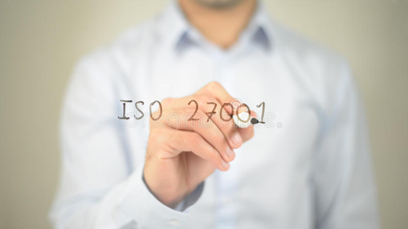 ISO 27001 , man writing on transparent screen royalty free stock photo