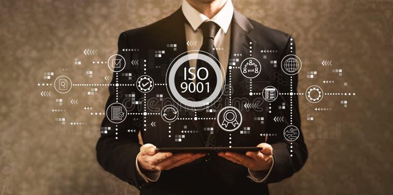 ISO 9001 med affärsmannen som rymmer en minnestavladator arkivfoton