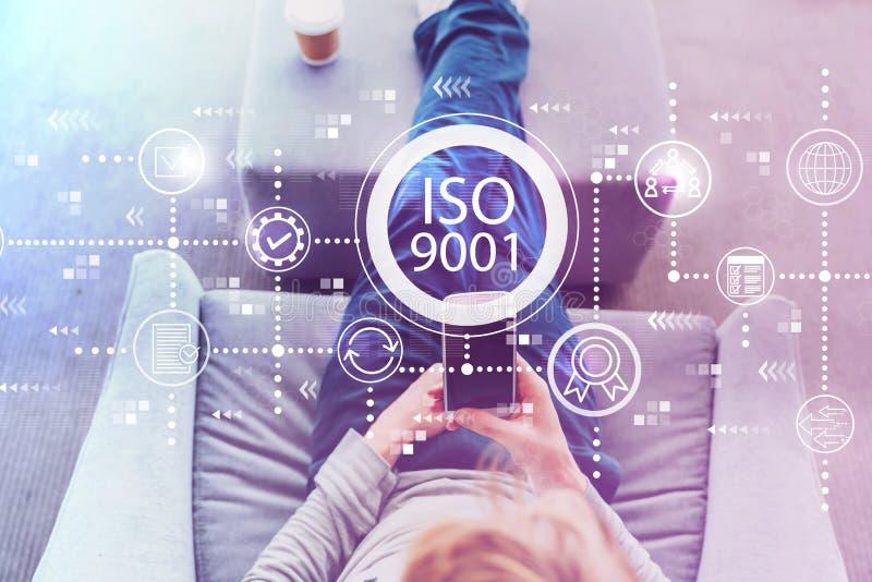 ISO 9001 med mannen som använder en smartphone fotografering för bildbyråer