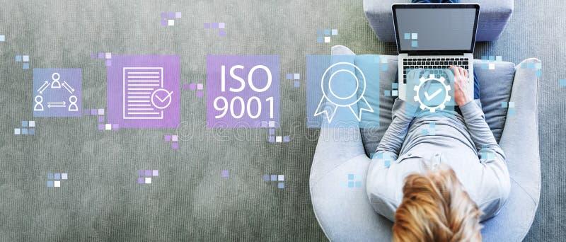 ISO 9001 med mannen som anv?nder en b?rbar dator fotografering för bildbyråer