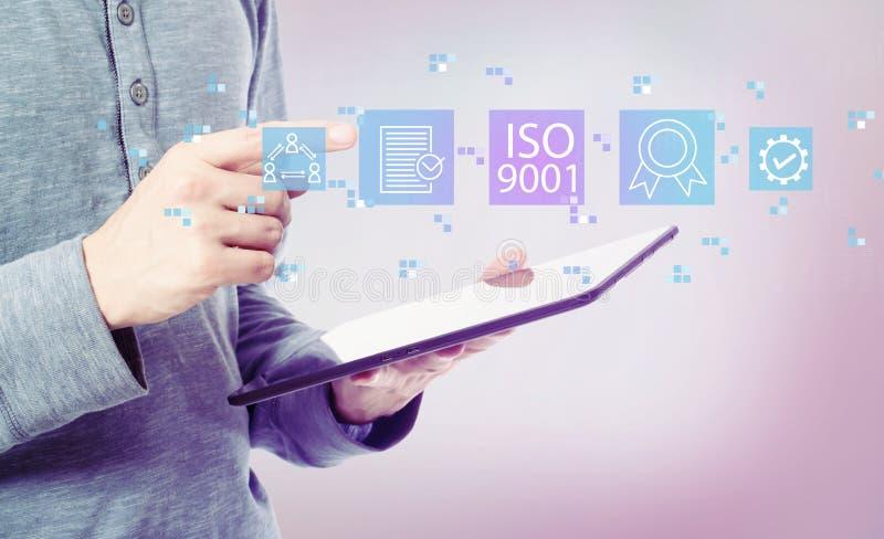 ISO 9001 med mannen som rymmer en minnestavla arkivbild