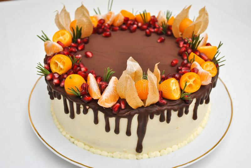 Isoalted födelsedagkaka med chokladisläggning och citrusgarnering Tangerinkaka, med granatäpplefrö close upp Efterrätt past arkivfoto
