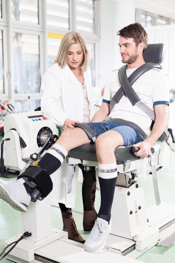 Isokinetic testing machines. Doctor physiotherapist is measuring a patient muscle strength for identify potentially harmful weaknesses stock photography