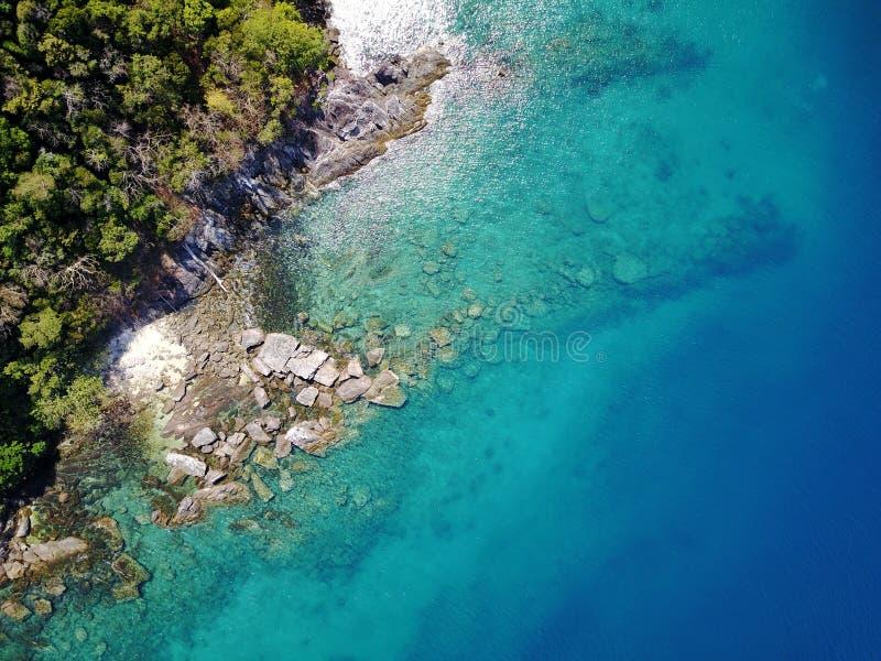 Isola con acqua cristallina che può vedere le rocce sotto fotografia stock