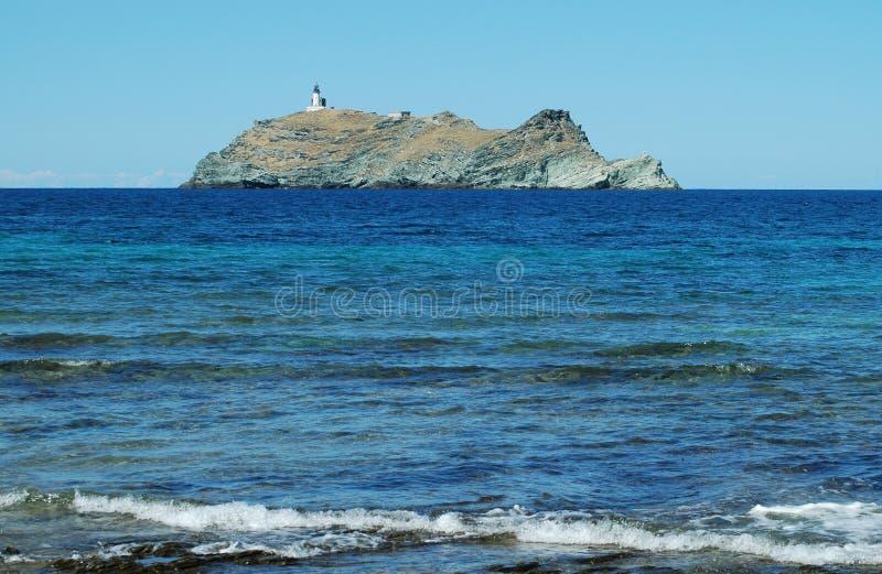 Isola con il faro vicino alla Corsica fotografia stock libera da diritti