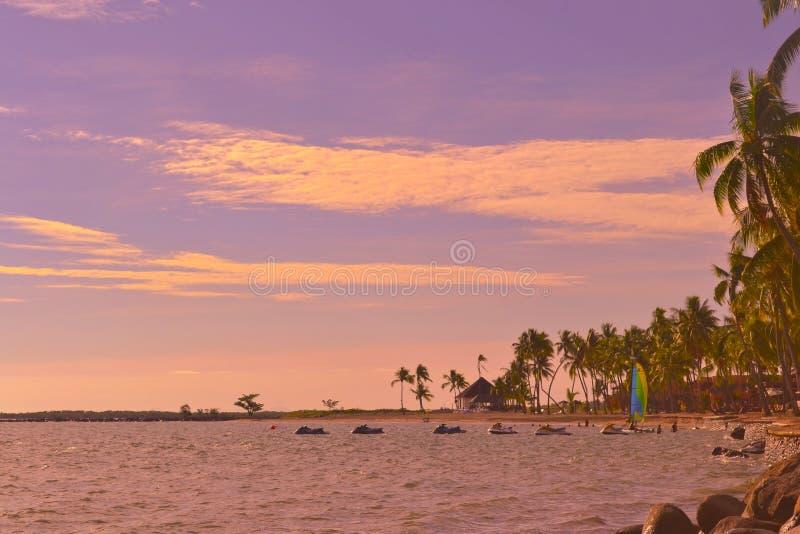 Isola di Denarau, Figi - giugno 24,2014: Cieli del getto nell'acqua al tramonto fotografie stock