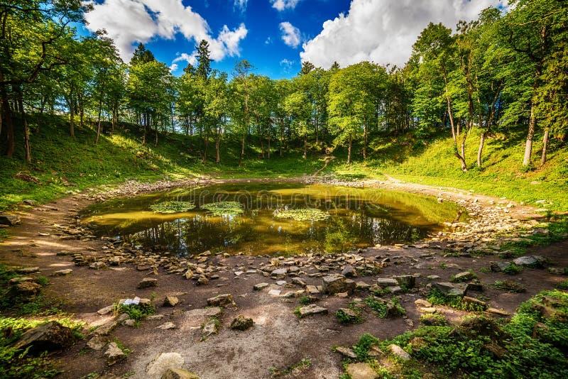 Isola di Saarema, Estonia: il cratere principale della meteorite nel villaggio di Kaali fotografia stock libera da diritti