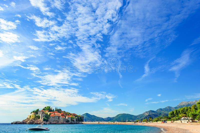 Isola di Sveti Stefan in Budua con una spiaggia in un bello giorno di estate, Montenegro fotografie stock libere da diritti