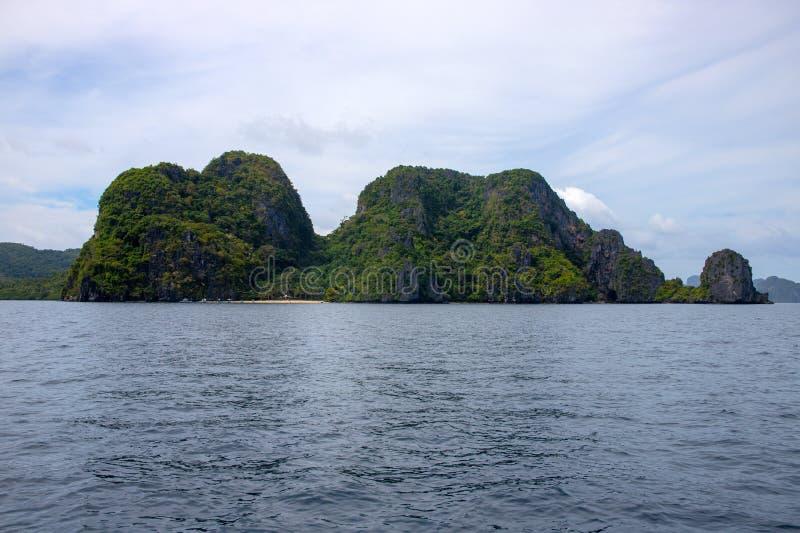 Isola tropicale in mare tranquillo Paesaggio marino della montagna verde Modello dell'insegna di luppolizzazione di isola di Fili fotografia stock libera da diritti