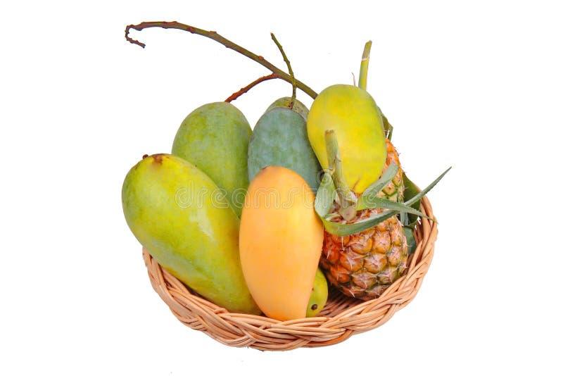 Isolado do fruto local tailandês como manga verdes, a manga madura, a manga doce e o abacaxi na cesta de madeira fotos de stock