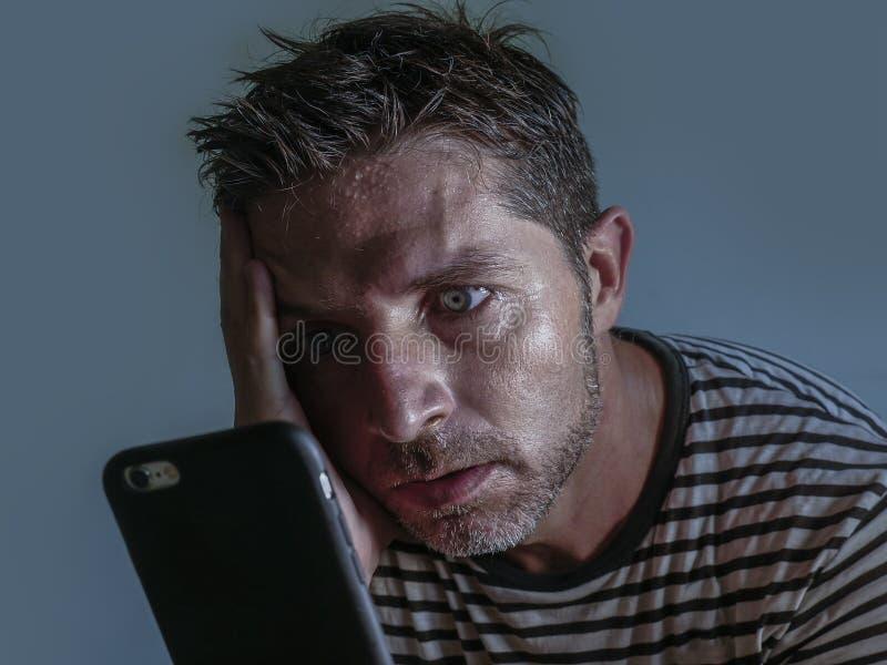 Isolado perto acima do retrato da cara do homem atrativo e forçado novo que usa o sentimento do telefone celular preocupou-se e f imagens de stock