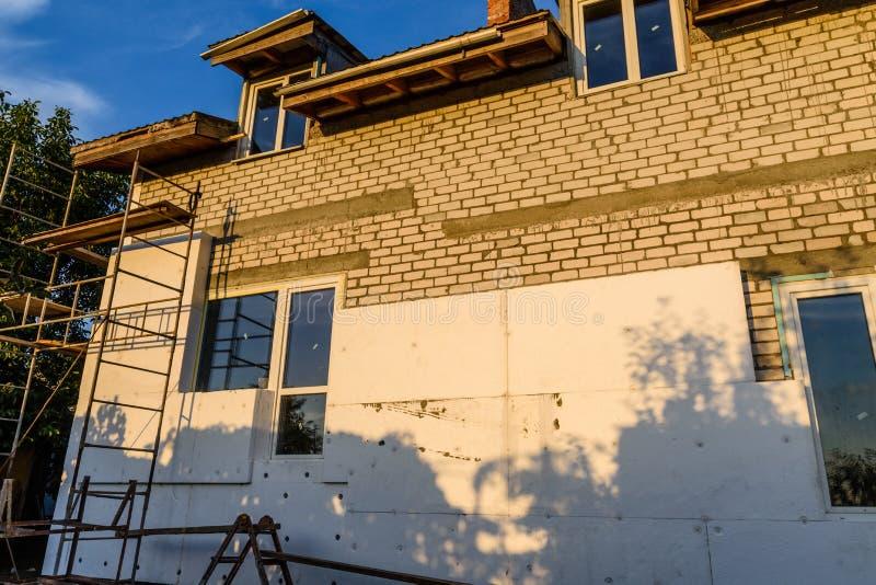 Isolamento della casa con schiuma di stirolo Impalcatura su costruzione immagine stock