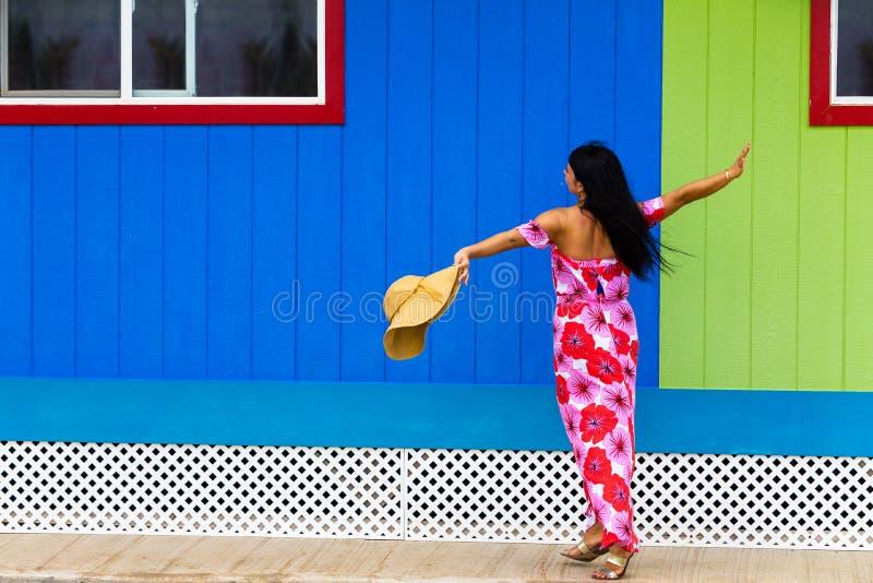 Isolano abbastanza polinesiano in un vestito floreale rosso fotografie stock