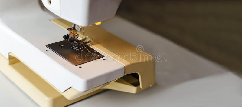 Isolat ?ber Wei? Arbeiten Sie durch das Licht der eingebauten Hardware-Lampe Stahlnadel mit Looper und presser Fu?nahaufnahme stockfotografie