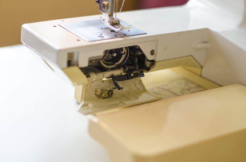 Isolat ?ber Wei? Arbeiten Sie durch das Licht der eingebauten Hardware-Lampe Stahlnadel mit Looper und presser Fu?nahaufnahme stockbilder