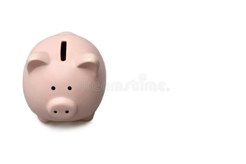isolat Das rosa Sparschwein steht auf einem lokalisierten weißen Hintergrund mit einem Schatten Gelbliche Blatt-Nahaufnahme stockbilder