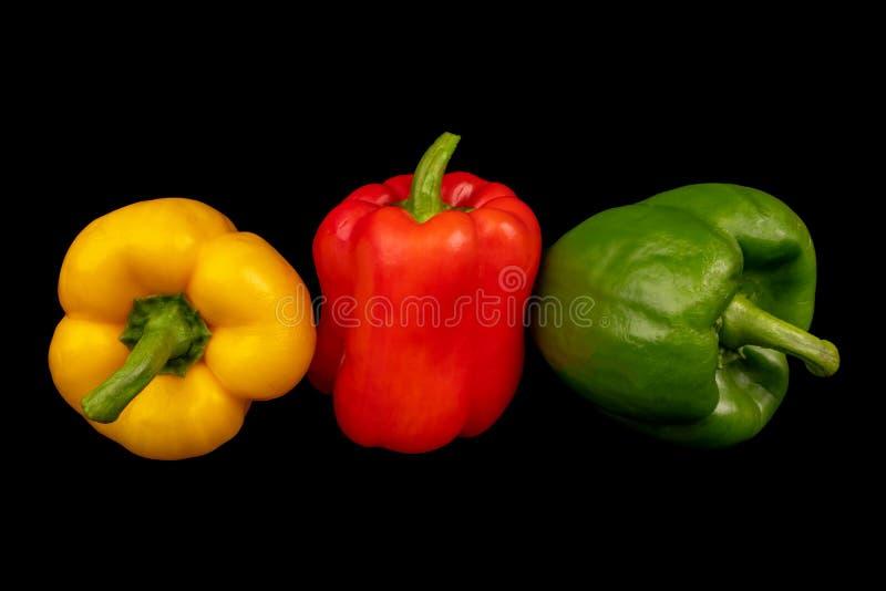 Isolat multicolore de poivrons de paprika sur le fond noir images stock