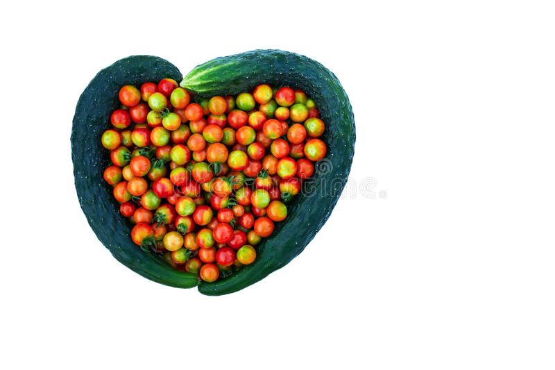 Isolate from cucumbers and cherry tomatoes in the form of a heart. stock photo