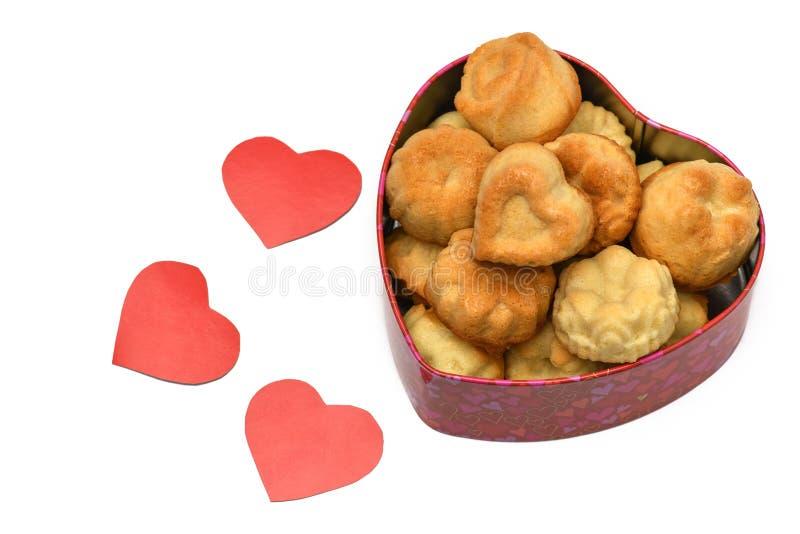 isolate valentin för dag s Ask i formen av en hjärta i den många muffin, kakor, lögn bredvid röd sniden hjärta tre royaltyfri bild