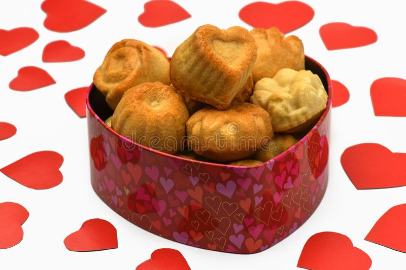 .Isolate. Valentine`s day. Box in the shape of a heart in it a lot of cupcakes, cookies, lie next to a lot of red carved hearts. stock images