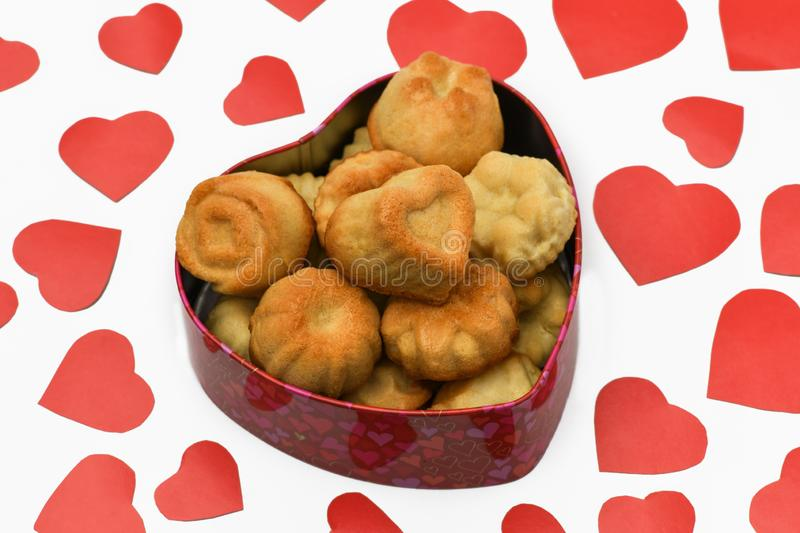 Isolate. Valentine`s day. Box in the shape of a heart in it a lot of cupcakes, cookies, lie next to a lot of red carved hearts. stock photography