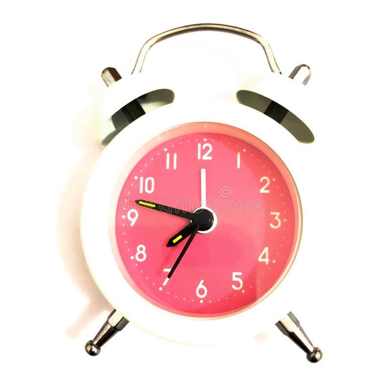 Isolated alarm clock on white table stock photography