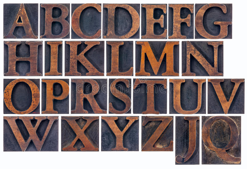 Isolated alphabet in wood type. Complete English alphabet in vintage wood type - a collage of 26 isolated letterpress printing blocks stained by ink royalty free stock photography