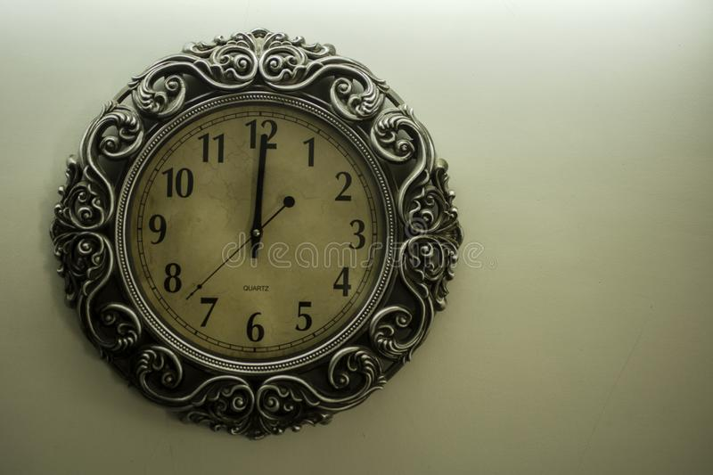 Isolated Ancient Designer Wall Clock With Light Yellow Back Ground showing time 12:00 o`clock and free spac on right side. Isolated Ancient Designer Wall Clock stock photos
