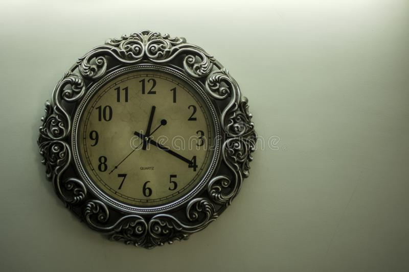 Isolated Ancient Designer Wall Clock With Light Yellow Back Ground showing time 12:20 o`clock and free spac on right side. Isolated Ancient Designer Wall Clock stock photos