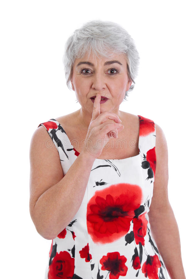 Isolated attractive mature woman making silence or attention gesture with her finger. royalty free stock photo