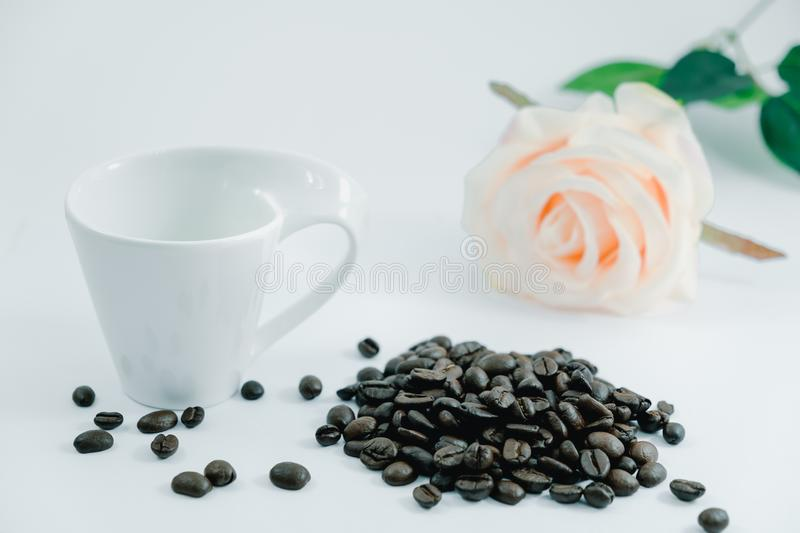 Isolated background coffee bean, rose and cup place on white tab royalty free stock images