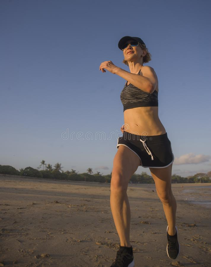 Isolated background portrait of young happy and attractive fit woman running on the beach in outdoors jogging workout in fitness t stock photo